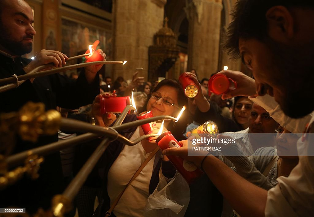 Greek Orthodox Christians light candles from their Patriarch and share the Holy Fire, which was brought from Jerusalem through Amman, at the Saint George church in downtown Beirut, on April 30, 2016. The Holy Fire is described by Orthodox Christians as a miracle that occurs every year at the Church of the Holy Sepulchre in Jerusalem on Great Saturday, or Holy Saturday, the day preceding Orthodox Easter. / AFP / PATRICK BAZ