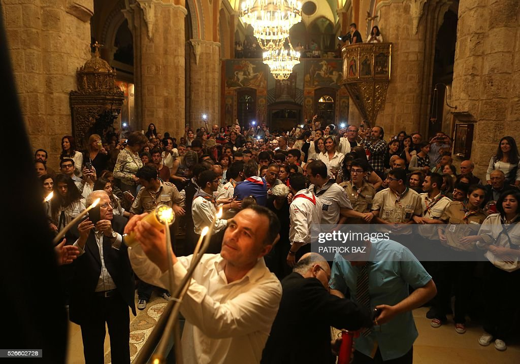 Greek Orthodox Christians share the Holy Fire, that was brought from Jerusalem through Amman, at the Saint George church in downtown Beirut on April 30, 2016. The Holy Fire is described by Orthodox Christians as a miracle that occurs every year at the Church of the Holy Sepulchre in Jerusalem on Great Saturday, or Holy Saturday, the day preceding Orthodox Easter. / AFP / PATRICK BAZ
