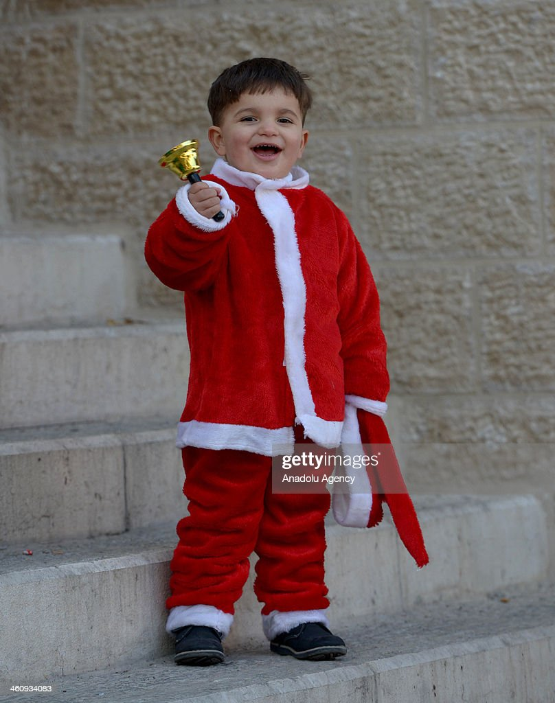 A Greek Orthodox kid in Santa Claus costume rings a bell during the Christmas at Nativity Church in Bethlehem, West Bank on January 6, 2014.