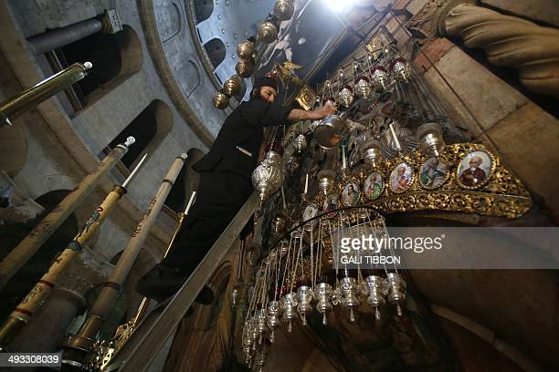 A Greek Orthodox monk pours oil into the lamps at the tomb of Jesus at the Church of the Holy Sepulchre in Jerusalem's Old City on May 23 2014 two...
