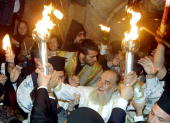 Greek Orthodox Patriach Kor Nilios spreads the holy fire in the Church of the Holy Sepulchre 14 April 2001 in Jerusalem Many pilgrims attended the...