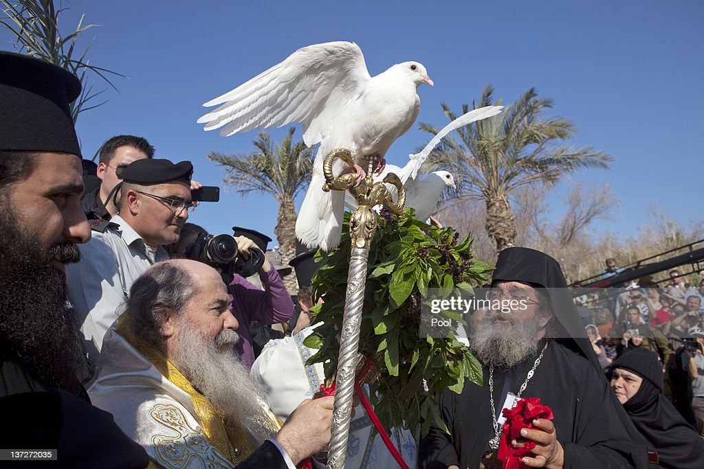 Greek Orthodox Patriarch of Jerusalem Metropolitan Theophilos holds his staff with a white dove balanced on the top as he is surrounded by priests and pilgrims during the Epiphany ceremony January 18,2012 at the Qaser al-Yahud baptismal site near Jericho, West Bank. Qaser al-Yahud is the spot where John the Baptist is said to have baptized Jesus. Thousands of pilgrims flocked to the holy site for the ceremony.