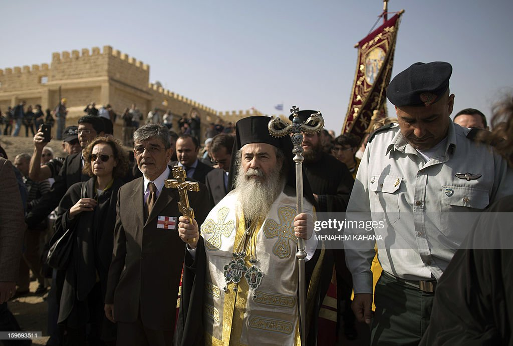 Greek Orthodox Patriarch of Jerusalem Theophilos III leads a march toward the Jordan River before a baptism ceremony as part of the Orthodox Feast of the Epiphany on January 18, 2013 at the Qasr al-Yahud baptismal site in the West Bank by the Jordan River. Theophilos III led a ceremony during which thousands of Orthodox Christians braved rain to plunge into plastic tubs filled with its murky water to celebrate Jesus's baptism.