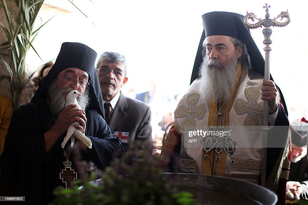 Greek Orthodox Patriarch of Jerusalem Theophilos III (R) looks on during a ceremony marking the Orthodox Feast of the Epiphany on January 18, 2013 at the Qasr al-Yahud baptismal site in the West Bank by the Jordan River. Theophilos III led the ceremony during which thousands of Orthodox Christians braved rain to plunge into plastic tubs filled with its murky water to celebrate Jesus's baptism.