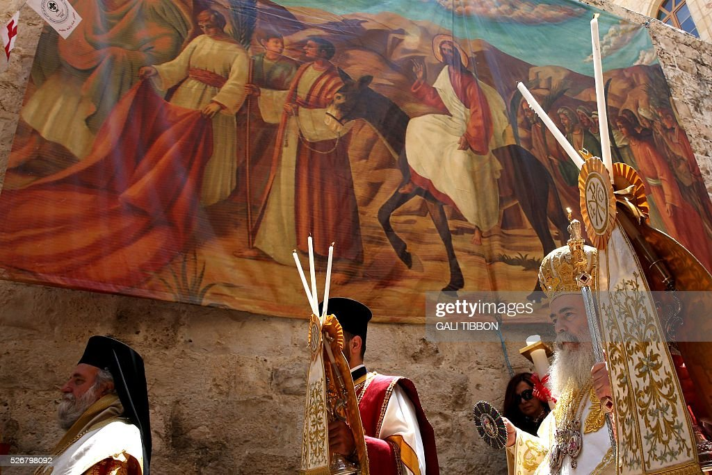 Greek Orthodox Patriarch of Jerusalem Theophilos III walks past Easter decorations during the Orthodox Easter Sunday procession to the Church of the Holy Sepulchre in Jerusalem's Old City on May 1, 2016 as Orthodox Christians celebrate the resurrection of Jesus. / AFP / GALI