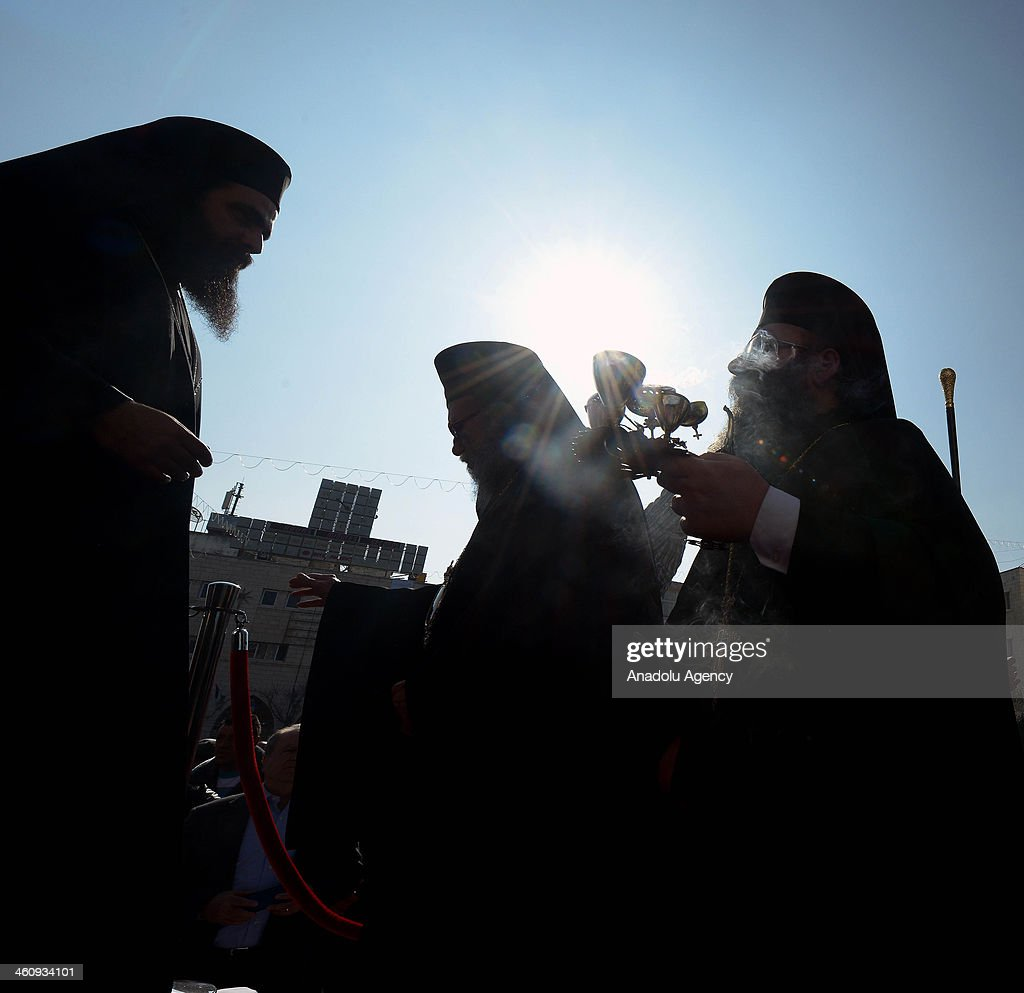 Greek Orthodox Patriarch Theophilos III (R) carries an incense during the Christmas mass at Nativity Church in Bethlehem, West Bank on January 6, 2014.