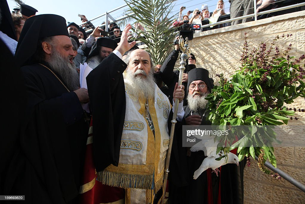 Greek Orthodox Patriarch Theophilos III of Jerusalem (C) prays next to a white dove during a traditional Epiphany ceremony at the baptismal site of Qasr el-Yahud near the West Bank city of Jericho on January 18, 2013. Thousands of Orthodox pilgrims come every year to the celebrate where it is believed that Jesus was baptised.