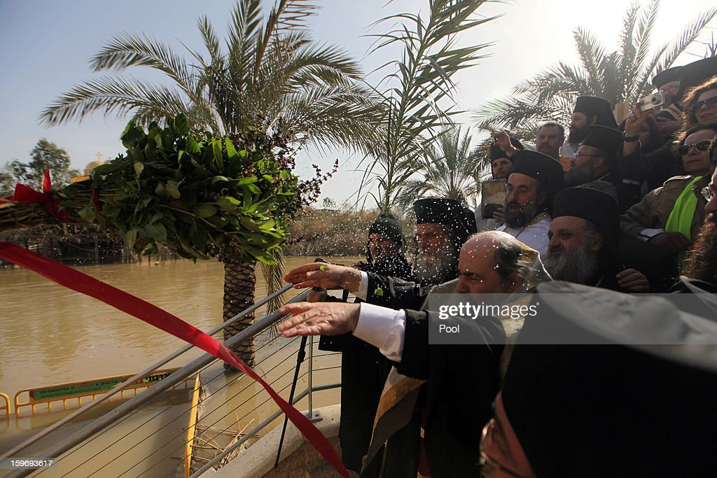 Greek Orthodox Patriarch Theophilos III of Jerusalem throws a wreath into the water and prays during a traditional Epiphany ceremony at the baptismal site of Qasr el-Yahud near the West Bank city of Jericho on January 18, 2013. Thousands of Orthodox pilgrims come every year to the celebrate where it is believed that Jesus was baptised.