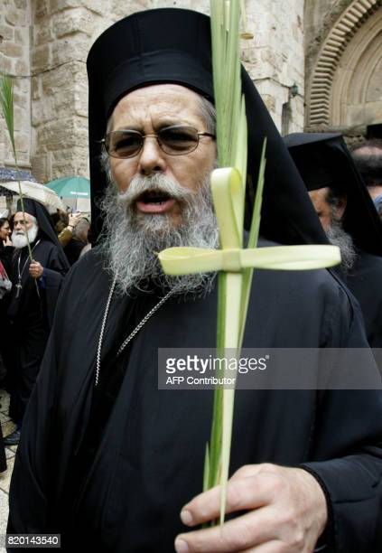 A Greek Orthodox priest carries a cross made from the leaf of a palm tree after the Palm Sunday procession at the Church of the Holy Sepulchre in...
