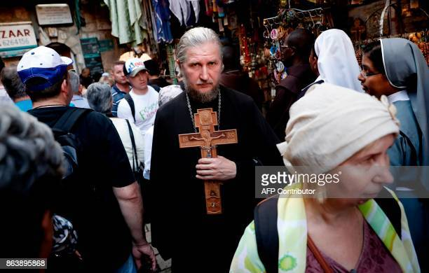 A Greek Orthodox priest carries a cross outside of the Church of the Holy Sepulchre in Jerusalems Old City during the Good Friday procession on...