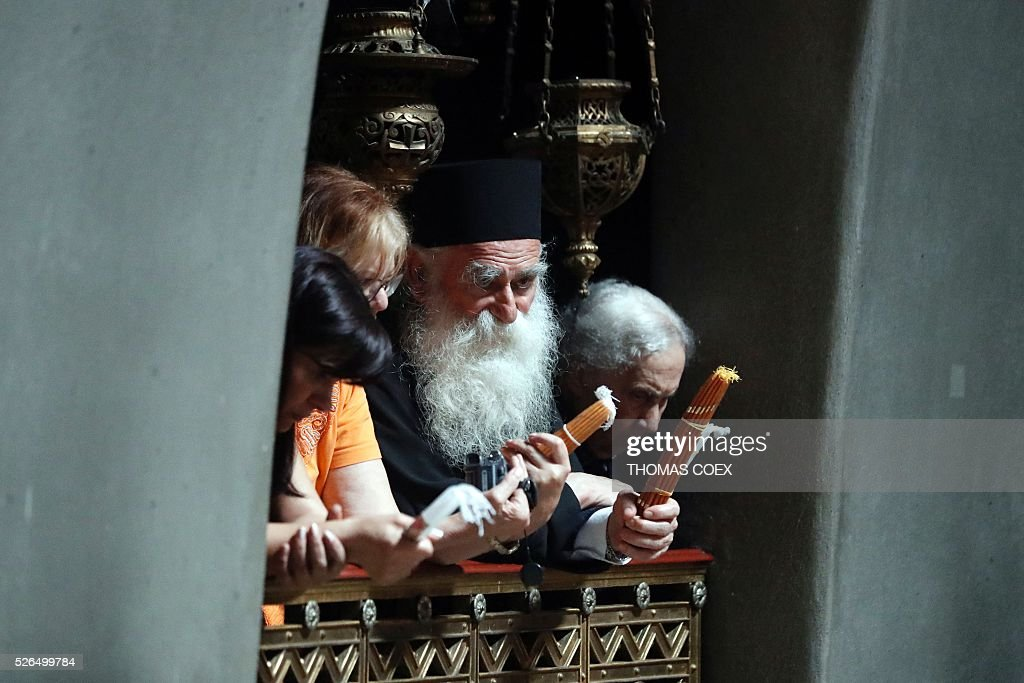 A Greek orthodox priest holds candles as thousands of Christian Orthodox worshippers gather in the Church of the Holy Sepulchre in Jerusalem's Old City, on April 30, 2016, during the Orthodox Easter ceremony of 'Holy Fire'. The ceremony celebrated in the same way for eleven centuries, is marked by the appearance of 'sacred fire' in the two cavities on either side of the Holy Sepulchre. / AFP / THOMAS