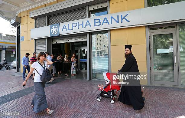 A Greek orthodox priest pushes a baby stroller past customers queuing to use an automated teller machine at an Alpha Bank AE bank branch in Athens...