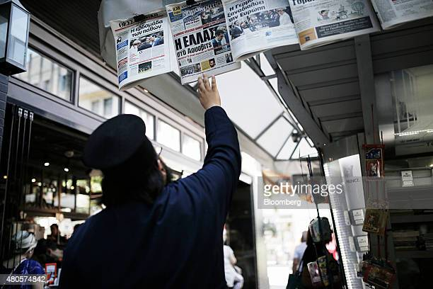A Greek orthodox priest reads the front page of a newspaper hanging outside a magazine kiosk in Thessaloniki Greece on Monday July 13 2015 Greece has...