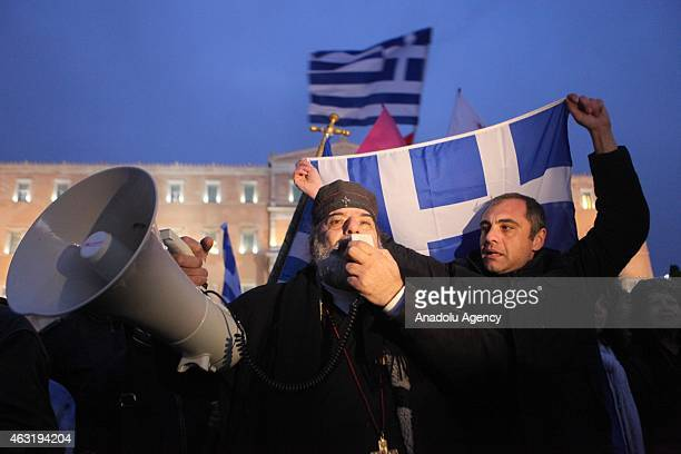 Greek Orthodox priest shouts slogans as he joins protesters gathering outside the Greek parliament building as they take part in a solidarity rally...