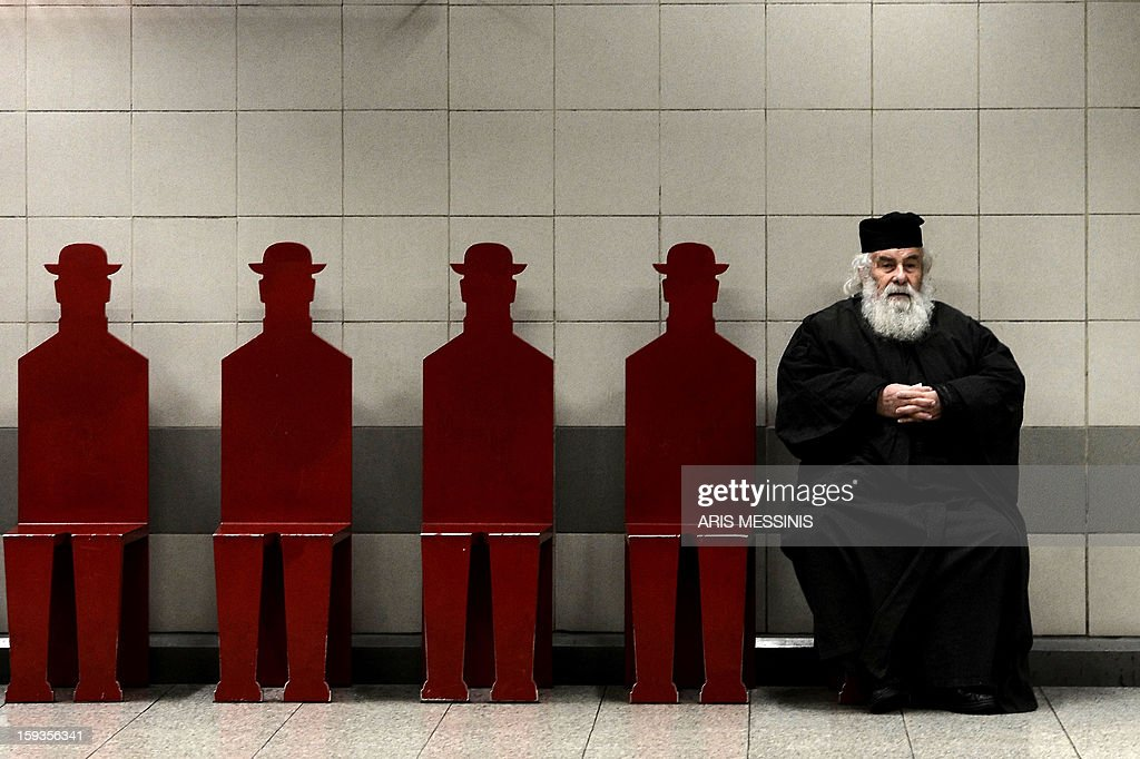 A Greek Orthodox priest sits on January 11, 2013 on a bench in an Athens metro station.