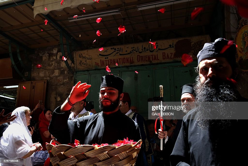 A Greek Orthodox priest throws rose leaves during the Orthodox Easter Sunday procession to the Church of the Holy Sepulchre in Jerusalem's Old City on May 1, 2016 as Orthodox Christians celebrate the resurrection of Jesus. / AFP / GALI