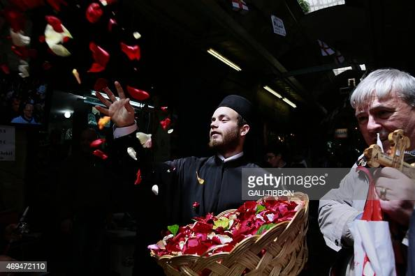 A Greek Orthodox priest throws rose petals during the Orthodox Easter Sunday procession to the Church of the Holy Sepulchre in Jerusalem's Old City...