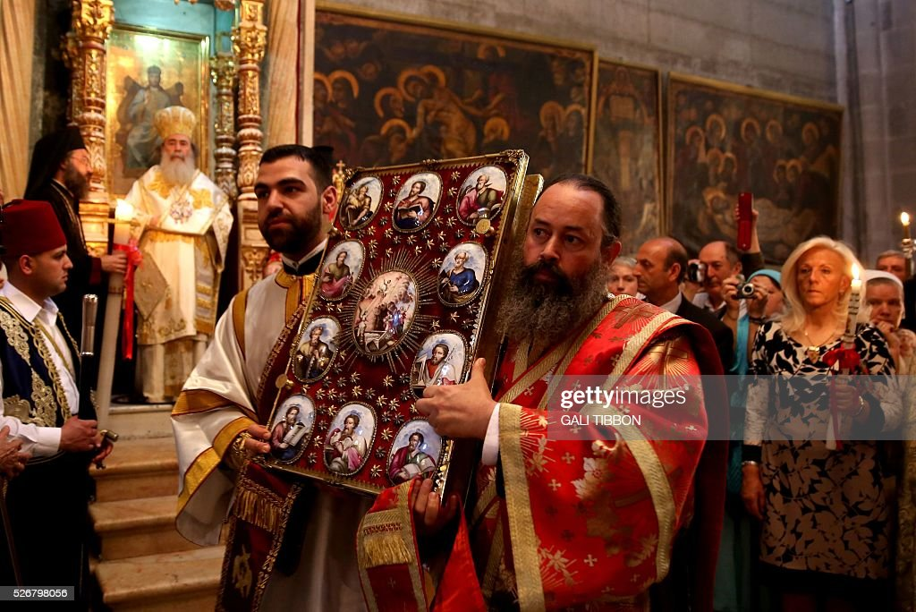 Greek Orthodox priests carry an ancient Bible book during the Orthodox Easter Sunday mass at the Church of the Holy Sepulchre in Jerusalem's Old City on May 1, 2016 as Orthodox Christians celebrate the resurrection of Jesus. / AFP / GALI