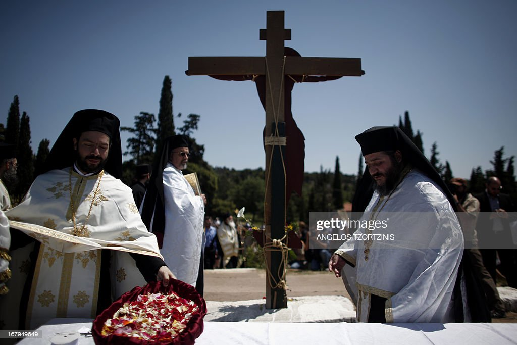 Greek Orthodox priests carry out the Apokathelosis, which forms a key part of Orthodox Easter, in a ceremony at the Church of the Dormition of the Virgin in Penteliin Penteli, north Athens on May 3 , 2013. Millions of Greeks flock to churches around the country this week to celebrate Easter, the country's foremost religious celebration. AFP PHOTO / Angelos Tzortzinis