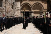 Greek Orthodox priests carry palm branches during Palm Sunday procession at the entrance of the Church of the Holy Sepulchre in Jerusalem's Old City...