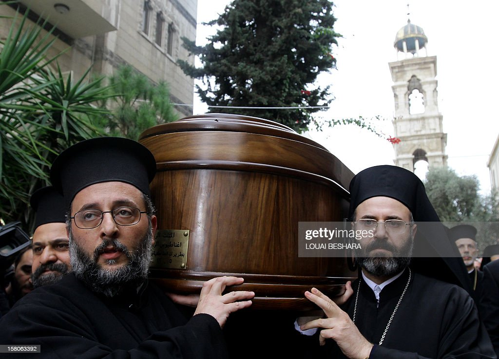 Greek Orthodox priests carry the coffin of Greek Orthodox patriarch of Syria, Ignatius IV Hazim, during his funeral in the Syrian capital Damascus on December 10, 2012. The patriarch died of a stroke in the Lebanese capital Beirut on December 5.