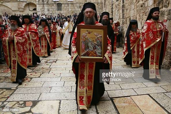 Greek Orthodox priests pray during the Orthodox Easter Sunday procession in front of the Church of the Holy Sepulchre in Jerusalem's Old City on...