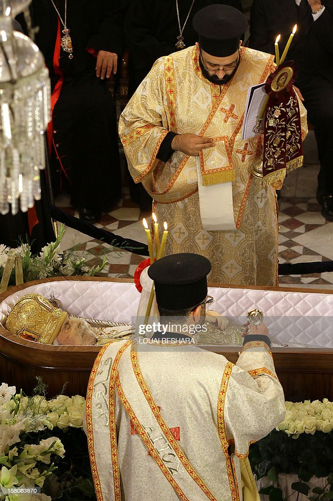 Greek Orthodox priests pray over the body of Greek Orthodox patriarch of Syria, Ignatius IV Hazim, during his funeral at the Meriamiah Church in the Syrian capital Damascus on December 10, 2012. The patriarch died of a stroke in the Lebanese capital Beirut on December 5.