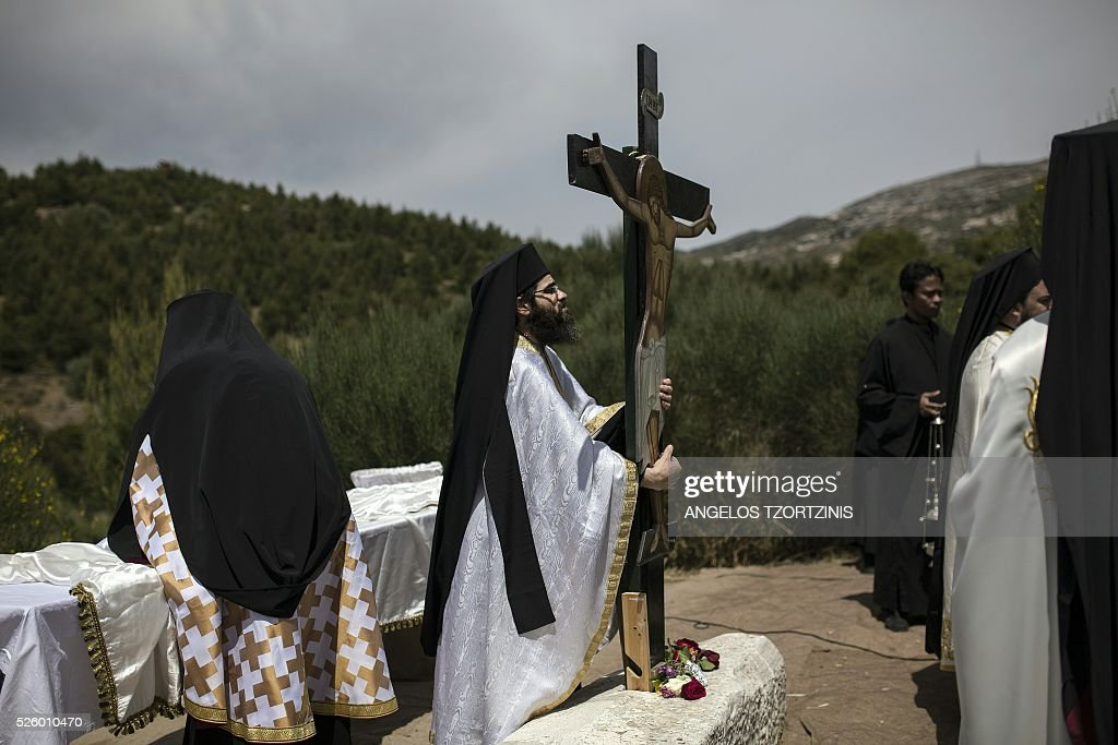 Greek Orthodox priests stand around of an image of Jesus crucified during the ceremony marking the Apokathelosis, the removal of Christ's dead body from the Cross, which forms a key part of Orthodox Easter, in a ceremony at the Church of the Dormition of the Virgin in Penteli, north Athens on April 29, 2016 Millions of Greeks flock to churches around the country this week to celebrate Easter, the country's foremost religious celebration. / AFP / ANGELOS