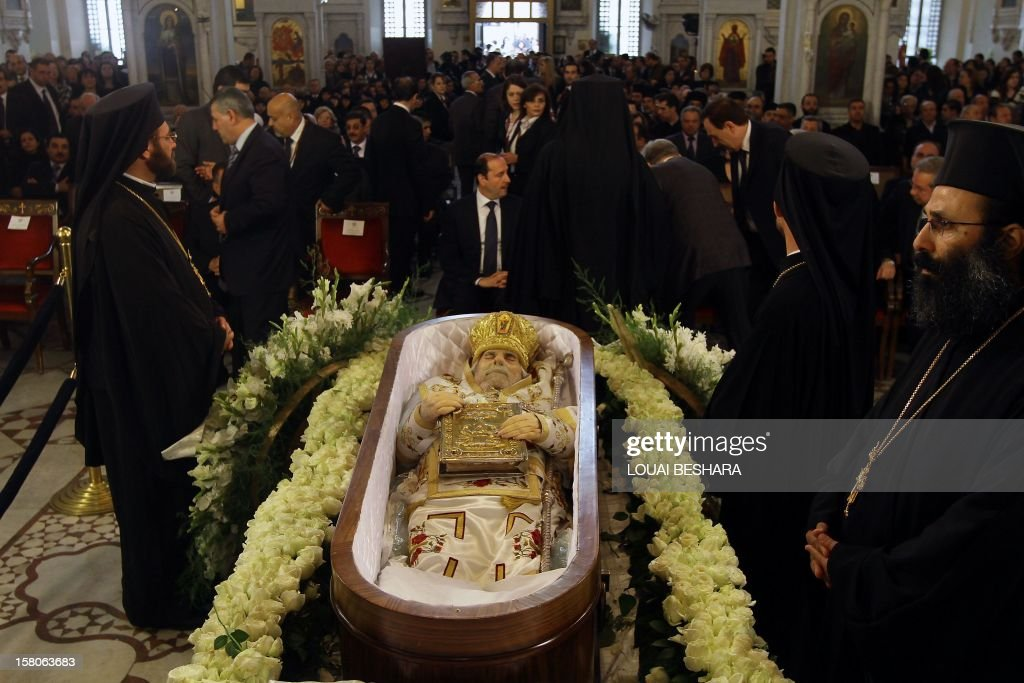 Greek Orthodox priests stand around the coffin of Greek Orthodox patriarch of Syria, Ignatius IV Hazim, during his funeral at the Meriamiah Church in the Syrian capital Damascus on December 10, 2012. The patriarch died of a stroke in the Lebanese capital Beirut on December 5.