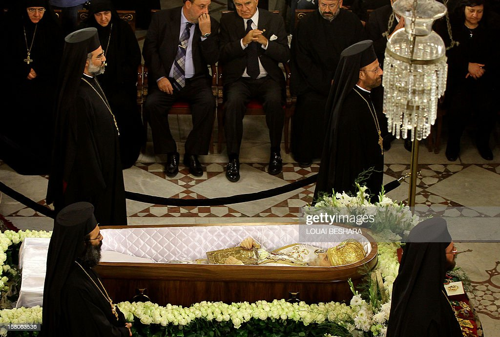 Greek Orthodox priests stand next to the coffin of Greek Orthodox patriarch of Syria, Ignatius IV Hazim, during his funeral at the Meriamiah Church in the Syrian capital Damascus on December 10, 2012. The patriarch died of a stroke in the Lebanese capital Beirut on December 5. AFP PHOTO/ LOUAI BESHARA
