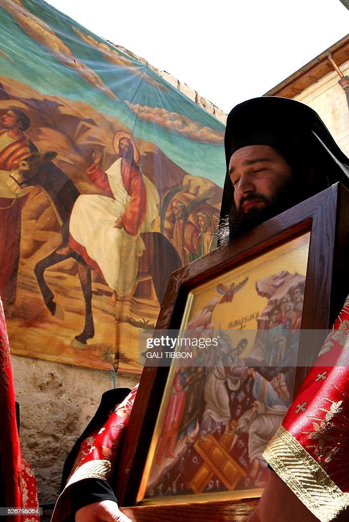 Greek Orthodox priests walk past Easter decoration during the Orthodox Easter Sunday procession to the Church of the Holy Sepulchre in Jerusalem's Old City on May 1, 2016 as Orthodox Christians celebrate the resurrection of Jesus. / AFP / GALI