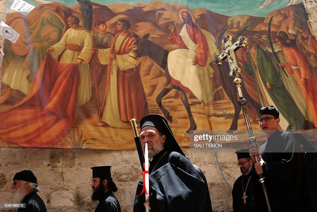 Greek Orthodox priests walk past Easter decorations during the Orthodox Easter Sunday procession to the Church of the Holy Sepulchre in Jerusalem's Old City on May 1, 2016 as Orthodox Christians celebrate the resurrection of Jesus. / AFP / GALI