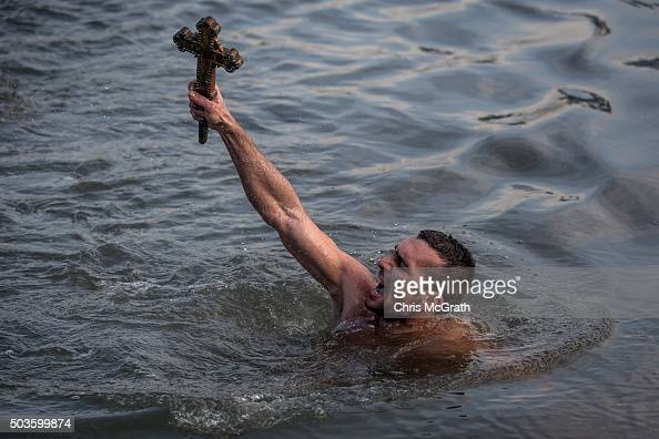 Greek Orthodox swimmer Nico Solis holds up a wooden cross after retrieving it from the Bosphorus river during the blessing of the water ceremony as...