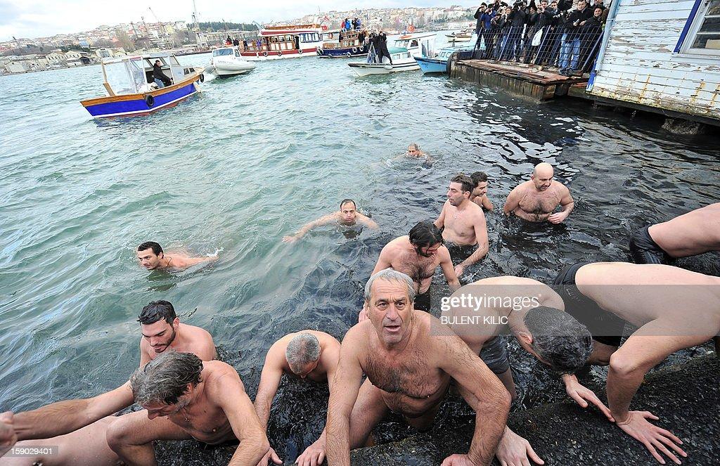 Greek Orthodox swimmers are back to the shore after the competition to retrieve the wooden cross from the Bosphorus river's Golden Horn after a mass as part of celebrations of the Epiphany day at the Church of Fener Orthodox Patriarchiate in Istanbul, on January 6, 2013. The Orthodox faith uses the old Julian calendar in which Christmas falls 13 days after its more widespread Gregorian calendar counterpart on December 25.