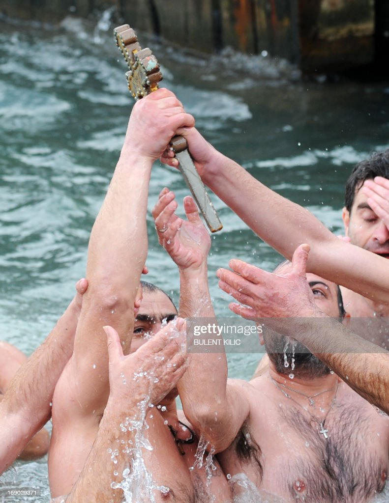 Greek Orthodox swimmers hold the wooden cross they retrieved from the Bosphorus river's Golden Horn after a mass as part of celebrations of the Epiphany day at the Church of Fener Orthodox Patriarchiate in Istanbul, on January 6, 2013. The Orthodox faith uses the old Julian calendar in which Christmas falls 13 days after its more widespread Gregorian calendar counterpart on December 25.