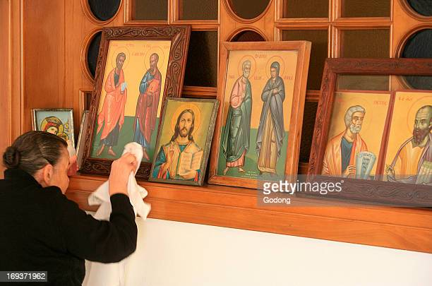 Greek orthodox woman cleaning icons