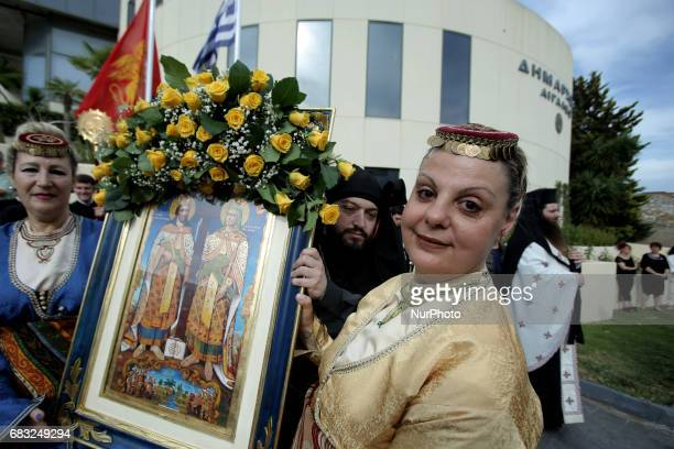 Greek Orthodox women dressed in traditional costumes hold a religious icon with Asent Constantine and St Helena attend the religious procession...