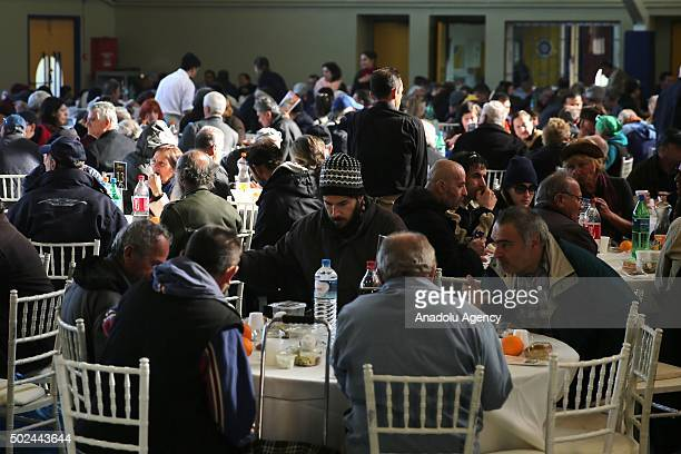 Greek people eat food distributed by the Athens Municipality for Christmas annual festival commemorating the birth of Jesus Christ in Athens Greece...