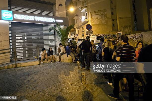 Greek people queue in front of an ATM mache to withdraw cash from a National Bank of Greece in central Athens on June 28 2015 Greece weighed drastic...