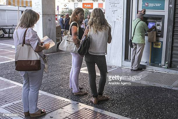 Greek people queue to withdraw money from an ATM outside a bank a day after the Greek bailout referendum in Athens Greece on July 06 2015 Greece has...