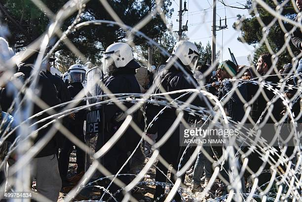 Greek police try to control stranded migrants as they try to cross GreekMacedonian border near the village of Idomeni Greece on December 3 2015 Since...
