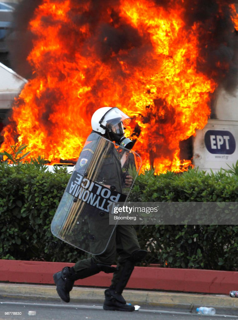 A Greek policeman runs past a burning vehicle set alight by protesters in Athens, Greece, on Saturday, May 1, 2010. Greek Finance Minister George Papaconstantinou said Greece faces 'unprecedented' budget cuts as the euro region and International Monetary Fund near approval of a bailout of as much as 120 billion-euro ($159 billion) for the debt-stricken nation. Photographer: Kostas Tsironis/Bloomberg via Getty Images