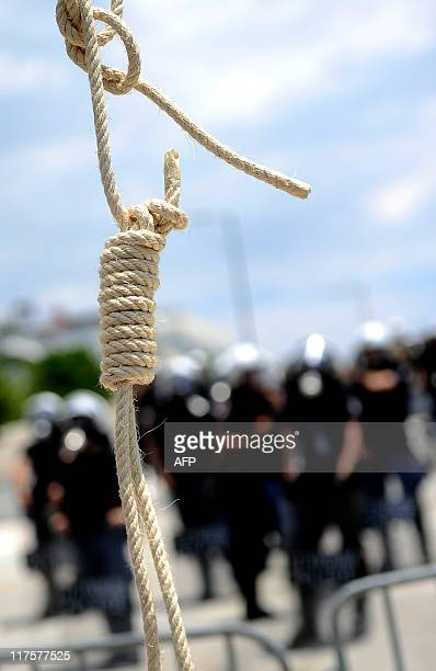 Greek policemen stand beside a fake gallows set by demonstrators in front of the Greek parliament on June 28 2011 in Athens during a protest part of...