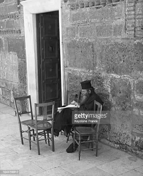 Greek pope reading the news from the front seated near the Byzantine door of an Orthodox church in Athens between 1940 and 1945