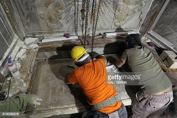 Greek preservation experts place back the marble slab stone that covered the Tomb of Jesus where his body is believed to have been laid after it was...