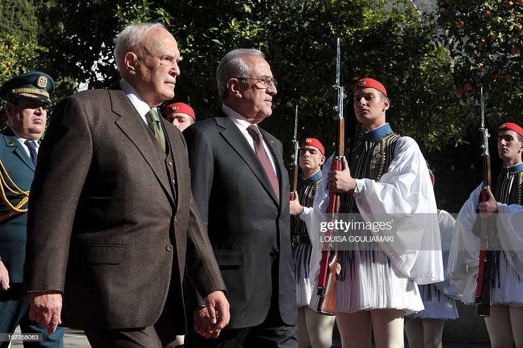 Greek President Carolos Papoulias (L) and his Lebanese counterpart Michel Sleiman inspect the presidental guard during an official welcoming ceremony outside the presidental palace in Athens on December 6, 2012. Lebanese president begun a three-day official visit to Greece for talks with political and business leaders.