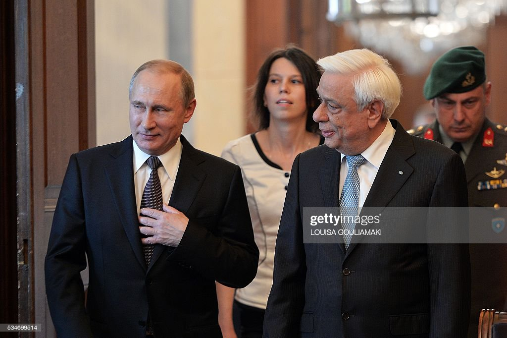Greek President Prokopis Pavlopoulos (R) and Russian President Vladimir Putin arrive for a meeting at the Presidential Palace on May 27, 2016, in Athens, as Putin is in Greece to reinforce a relationship with one of his few friends in the EU amid continuing diplomatic tensions with the West. The visit -- Putin's first to the EU since December -- comes as the bloc's leaders are to discuss next month whether to renew sanctions on Russia's banking, defence and energy sectors that expire in July. / AFP / LOUISA