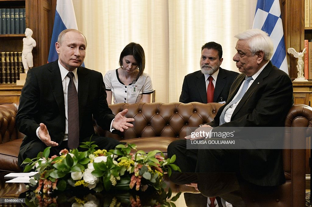 Greek President Prokopis Pavlopoulos (R) talks with Russian President Vladimir Putin during their meeting at the Presidential Palace on May 27, 2016, in Athens, as Putin is in Greece to reinforce a relationship with one of his few friends in the EU amid continuing diplomatic tensions with the West. The visit -- Putin's first to the EU since December -- comes as the bloc's leaders are to discuss next month whether to renew sanctions on Russia's banking, defence and energy sectors that expire in July. / AFP / LOUISA