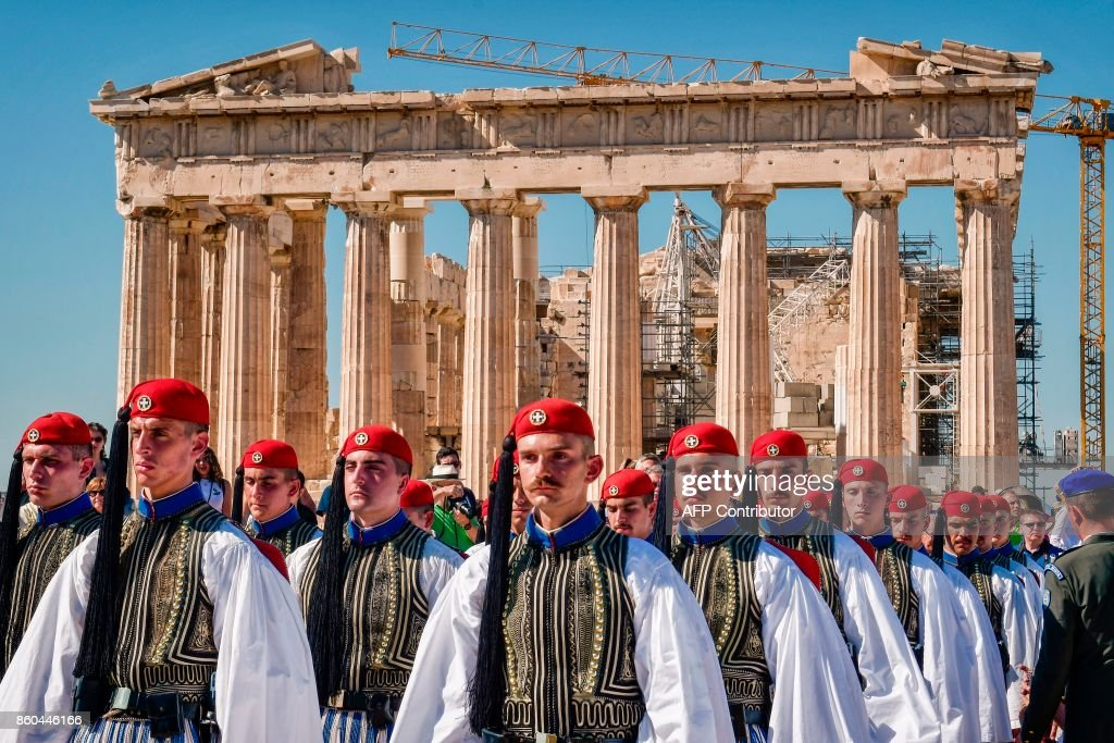 Greek presidental Evzoni Guards stand in front the Parthenon temple atop the Acropolis hill during a ceremony marking the anniversary of the liberation of Athens from Nazi occupation, on October 12, 2017 in Athens. /
