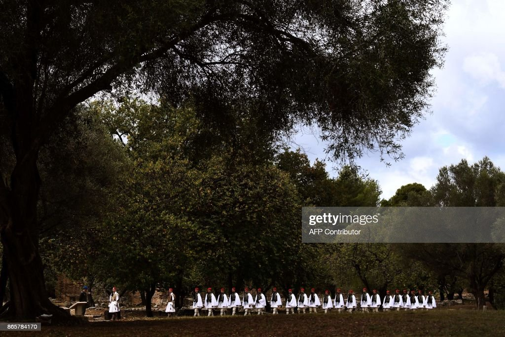 Greek Presidential guards, or Evzones, walk across the ancient archeological site at the Temple of Hera in Olympia on October 24, 2017 during the lighting ceremony of the Olympic flame for the 2018 Winter Olympics in Pyeongchang, South Korea. The 2018 Winter Olympics will take place from February 9 until February 25, 2017. /